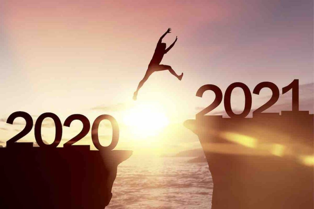 man is jumping over the precipice that separates 2020 from 2021