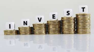 growing pile of money with the word invest at the top