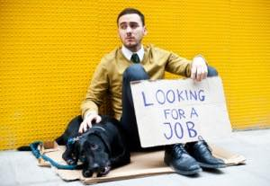 man is sitting on a corner with his dog and a cardboard with the writing:looking for a job