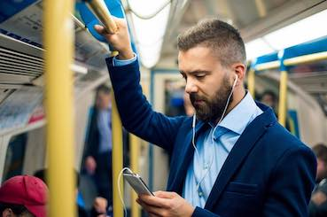 man is listening to the music in a train while is going to work