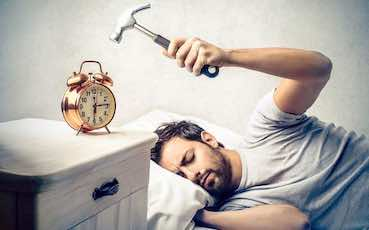man in a bed with a hammer in his hand ready to destroy the alarm clock
