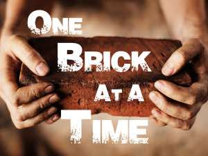 two hands are holding one brick