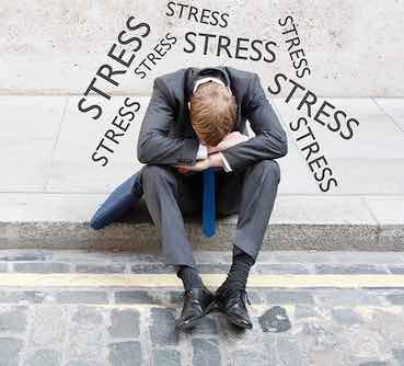 stressed man is sitting on the sidewalk in despair
