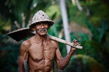 Old Japanese man with a shovel on his shoulder