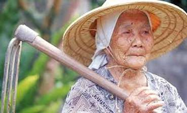 Old Japanese woman with a shovel on her shoulder