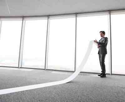 Businessman is keeping and unrolling an endless list of goals