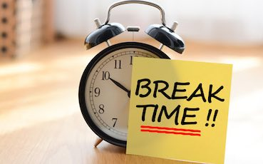 small paper glued to a clock saying: break time!!