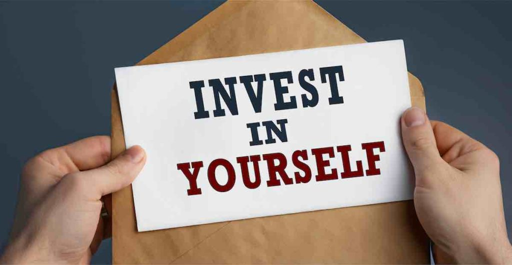 two hands hold a letter with writing: invest in yourself