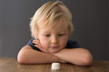 kid is looking to a marshmallow