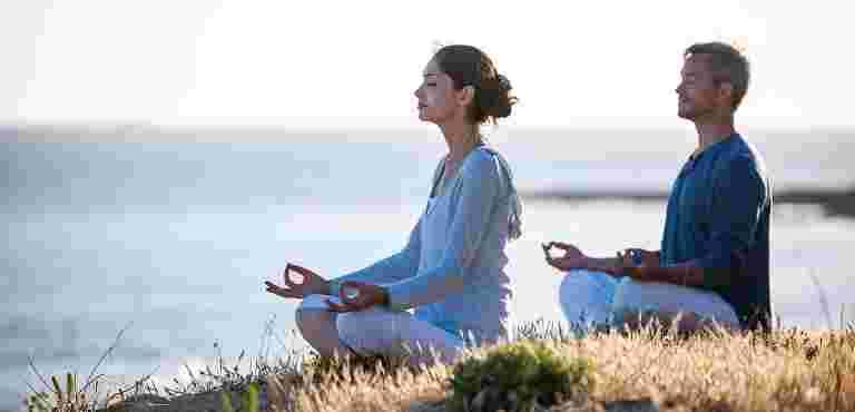 man and woman meditating close to the sea