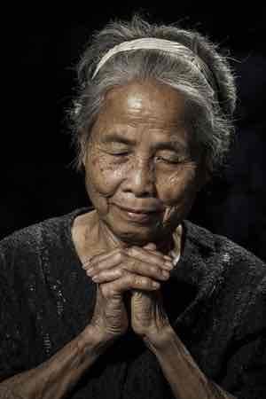 elderly woman is praying