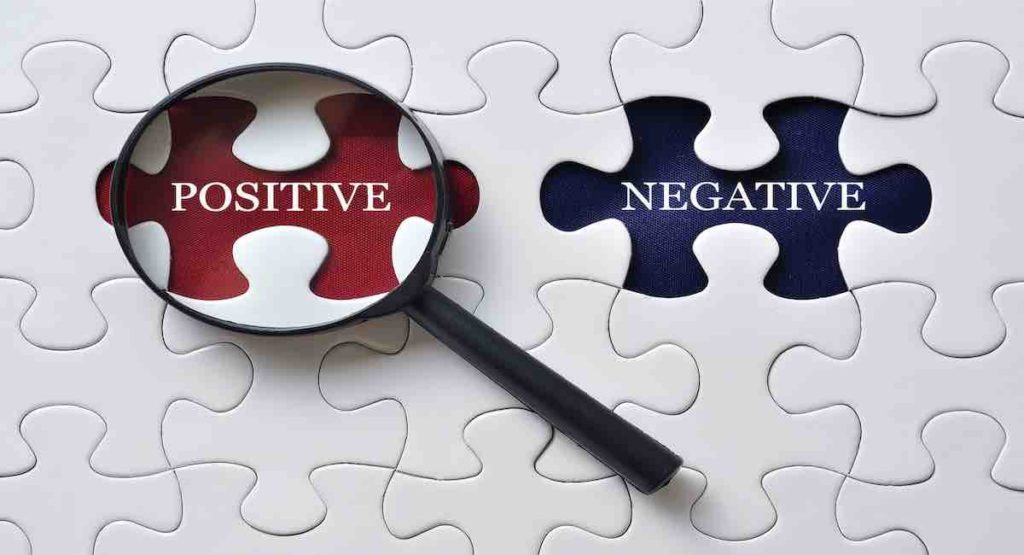 Magnifying glass on the missing puzzle with word POSITIVE/NEGATIVE