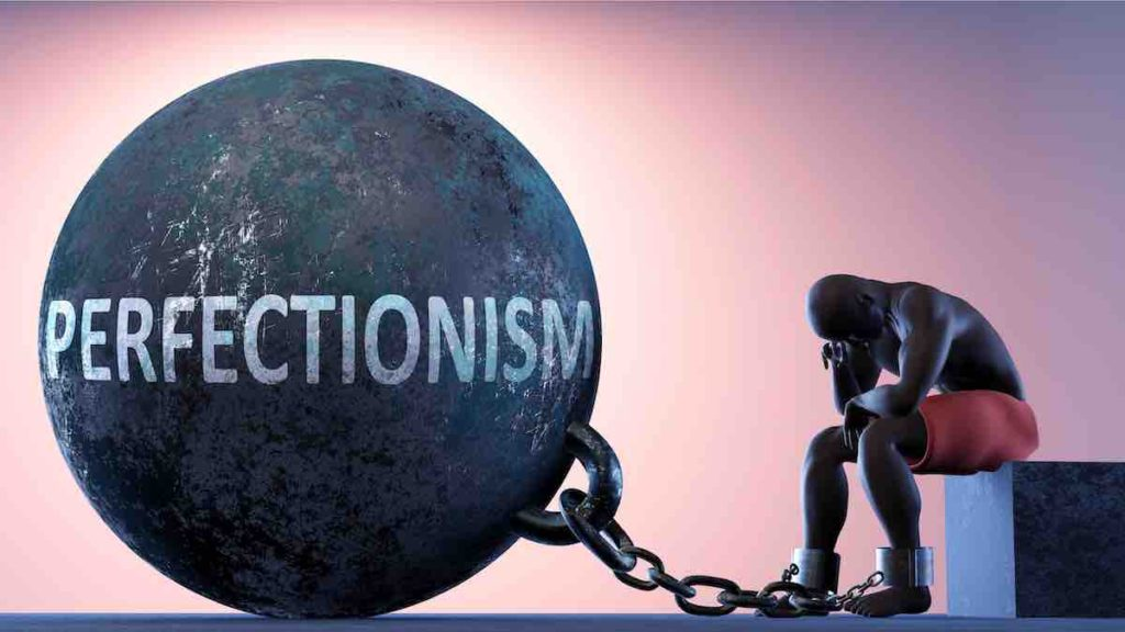 Perfectionism as a heavy weight in life - symbolized by a person in chains attached to a prisoner ball
