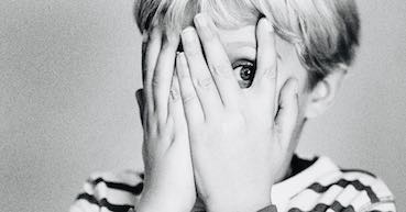 scared child covering his eyes