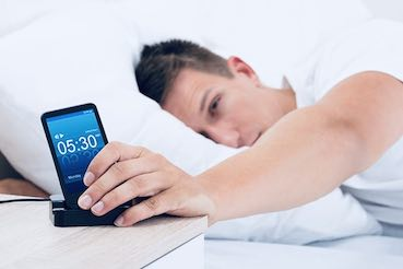 man in bed is hitting the snooze button
