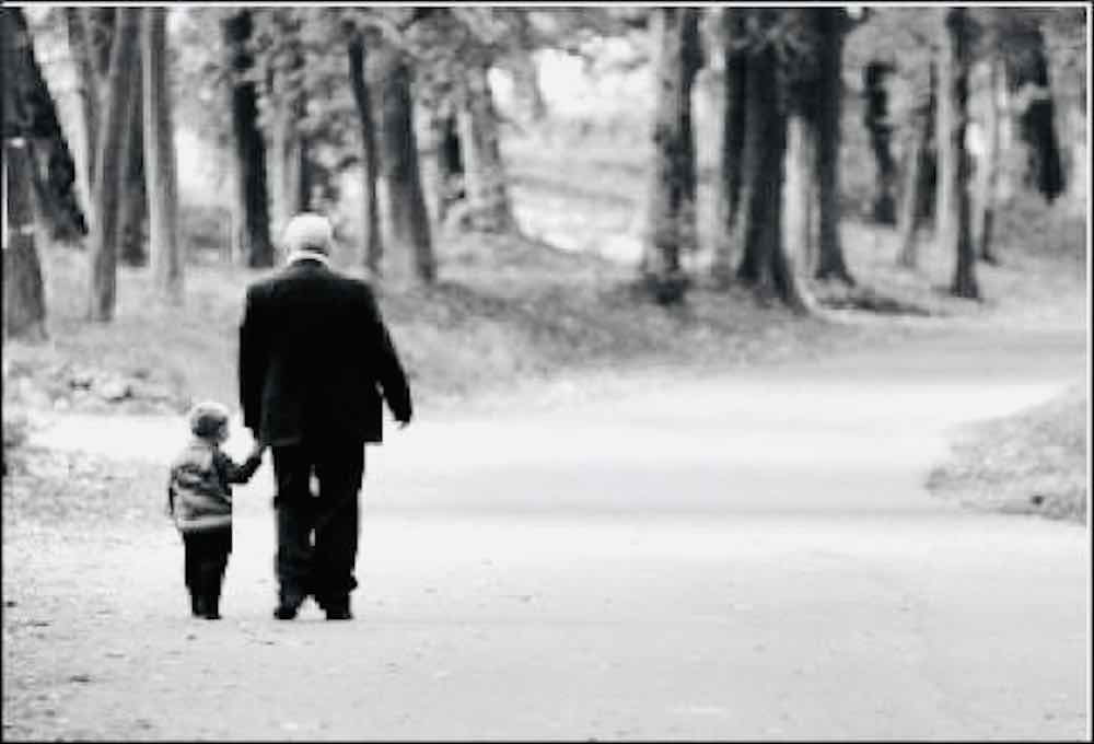 Boy and grandfather holding each other hands