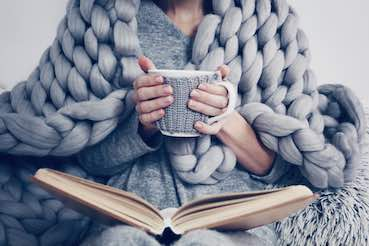 woman reading book while enjoying cup of tea