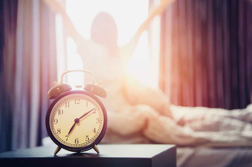 woman is waking up thanks to an alarm clock