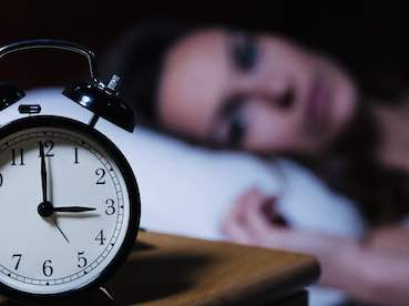 alarm clock in foreground with woman in bed in background