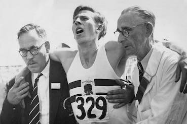 Roger Bannister helped by doctors at the finish line