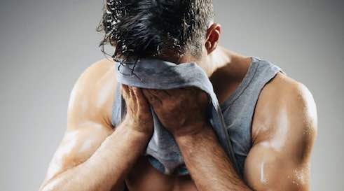 man wiping sweat from his face with t-shirt
